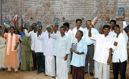 Indians hold Bible outside their local church where many villages are coming to learn and baptize others as a result of Bible training.